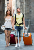 Couple in shorts with luggage walking through city Royalty Free Stock Photography