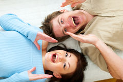 Couple shouting through megaphone shaped hands Stock Photos