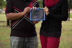 Couple showing blackboard. At garden Stock Photos