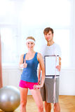 Couple showing clipboard with measuring tape. Healthy couple in sportswear showing clipboard with measuring tape Royalty Free Stock Images