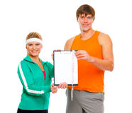 Couple showing clipboard with measuring tape. Healthy couple in sportswear showing clipboard with measuring tape isolated on white Stock Photo