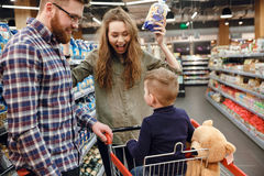 Couple showing convenience food to their son. Young Couple showing convenience food to their son in supermarket stock photography
