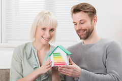 Couple Showing Energy Efficiency Rate On House Model Stock Photography