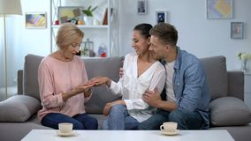 Couple showing engagement ring to future mother-in-law, happy family relations. Stock footage stock video