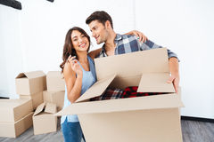 Couple showing keys to new home and hugging Stock Photo