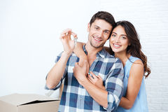 Couple showing keys to new home hugging looking at camera. Young smiling couple showing keys to new home hugging looking at camera stock images