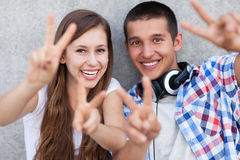 Couple showing peace sign. Portrait of young couple outdoors Royalty Free Stock Images