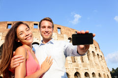 Couple showing smartphone in Rome by Colosseum Stock Image