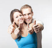 Couple showing thumbs up. Young couple showing both thumbs up smiling-  on gray Stock Photo