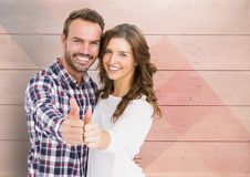 Couple showing thumbs up against wooden background Stock Image