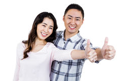 Couple showing thumbs up while standing. Against white background Royalty Free Stock Image