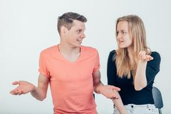 Couple shrugging their shoulders having uncertainty not knowing what to do. Half length portrait of young couple standing against white background shrugging Royalty Free Stock Photo