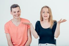 Couple shrugging their shoulders having uncertainty not knowing what to do. Half length portrait of young couple standing against white background shrugging Stock Image