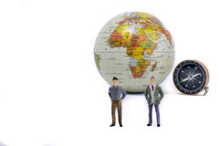 A couple by the side of a globe. With a compass on isolated white background Stock Photography