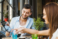 Couple in sidewalk cafe and using digita tablet. Stock Images