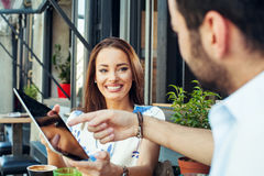 Couple in sidewalk cafe and using digita tablet. Stock Photos