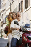Couple Sightseeing On Scooter. Happy middle aged couple sightseeing on scooter in Rome; Italy Royalty Free Stock Images