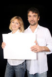 Couple with sign. Young married couple, holding up an empty poster royalty free stock photos