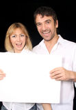 Couple with sign. Young married couple, holding up an empty poster stock photo