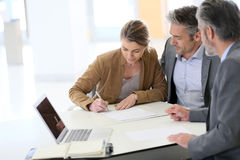 Couple signing contract in bank Stock Photo
