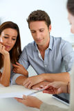 Couple signing contract with real estate agent. Future property owners reading terms of contract Stock Photography