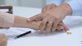 Couple signing divorce policy, woman taking off engagement ring from finger. Stock footage stock footage