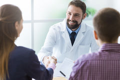 Couple signing a document at doctor's office Royalty Free Stock Photos
