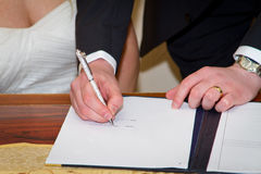 Couple signing marriage registration form. Married couple signing marriage registration form Royalty Free Stock Photography
