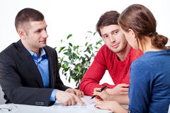 Couple signing the mortgage agreement Stock Photos