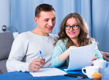 Couple signing papers. Husband and wife preparing beneficial agreement papers together at home Stock Photos