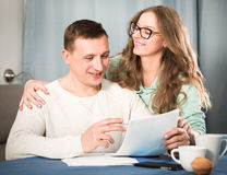 Couple signing papers. Middle-aged couple signing beneficial financial agreement together at home Royalty Free Stock Images