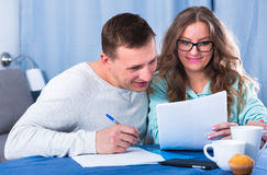 Couple signing papers. Middle-aged couple signing beneficial financial agreement together at home Royalty Free Stock Photo