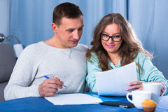 Couple signing papers. Middle-aged couple signing beneficial financial agreement together at home Royalty Free Stock Image