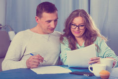 Couple signing papers. Middle-aged couple signing beneficial financial agreement together at home Stock Photography