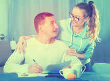 Couple signing papers. Smiling middle-aged husband and wife signing agreement papers together at home Royalty Free Stock Photo