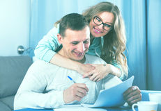 Couple signing papers. Smiling middle-aged husband and wife signing agreement papers together at home Stock Photo