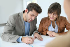 Couple signing property agreement Stock Photography