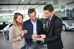 Couple signing a purchase contract on tablet Royalty Free Stock Image