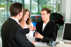 Couple signing sales contract at car dealer Royalty Free Stock Image