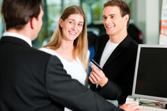 Couple signing sales contract at car dealer Stock Photos
