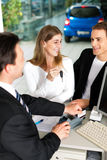Couple signing sales contract at car dealer Stock Photography