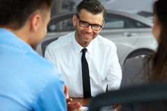 Couple Signing Salesman Contract. Car Showroom Royalty Free Stock Images