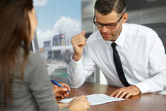 Couple Signing Salesman Contract. Car Showroom Royalty Free Stock Photography