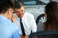 Couple Signing Salesman Contract. Car Showroom Stock Photos