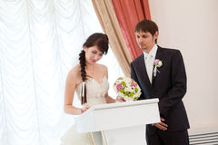 Bride and groom signing a wedding document Stock Photo