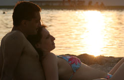 Couple silhouette. Young couple laying on the  sunset beach Royalty Free Stock Photography