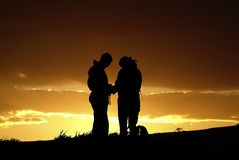 Couple silhouette. Two people silhouetted against dramatic skyline stock image
