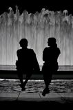 Couple silhouette. This picture represents a silhouette of couple sitting behind the water fountain in a park Royalty Free Stock Photography