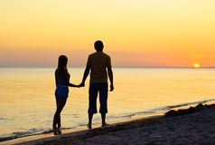 Couple silhouette on the beach. At sunset Royalty Free Stock Image