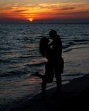 Couple silhouette on beach against sunset Royalty Free Stock Images